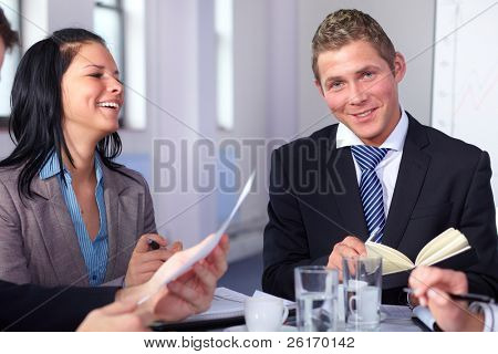 Two young business people sitting at table and have laugh while working on some paperwork