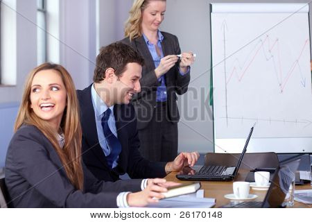 Team of 3 young business people during meeting, two of them sitting at conference table while one woman just finish her presentation