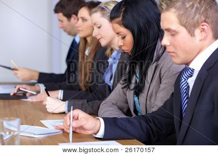 Team of 5 young people sitting at conference table and work on some paperwork, focus on female with black hair
