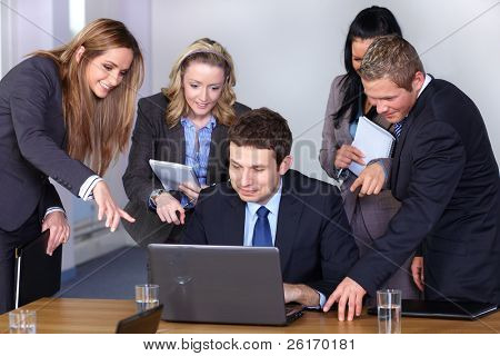 Team of 5 business people behind young businessman sitting and working on his laptop