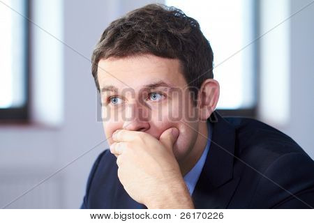 Young stressed and worried businessman, looking away, sad face expression.