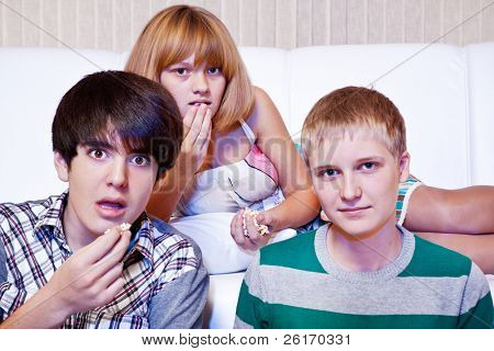 Amazed teens eat popcorn while watching movie