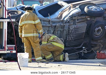 Firefighters investigating a Car Wreck with a car rolled over