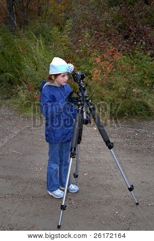 Little girl with tripod and camera taking pictures