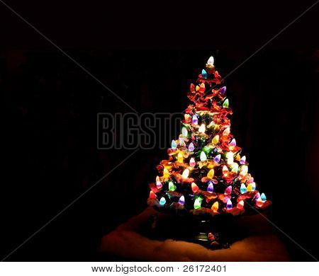 Christmas tree decorated with glowing colored lights and black background