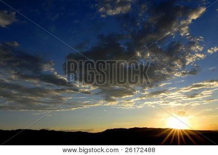 Sunset with sun and clouds in orange and golden light