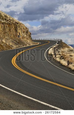 Country road with painted double yellow lines going up hill
