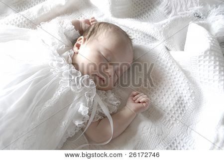 New born baby girl dressed in white asleep on a white blanket