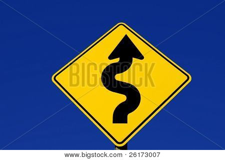Yellow street sign with curves against blue sky