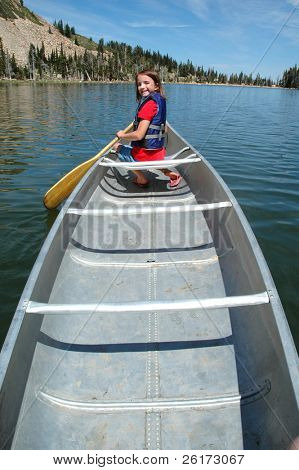 Young girl canoeing in lake with paddle