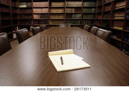 Conference room table with several leather chairs and shelves of books