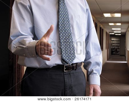 Business man reaching to shake hands in office