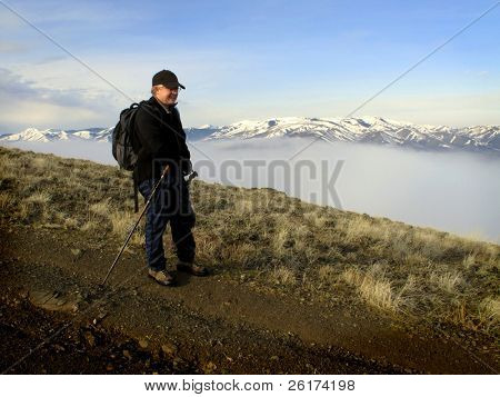 One person walking with valley and fog with mountains in background