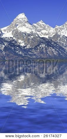 Detail of Grand Tetons Mountains with blue sky and tourist looking