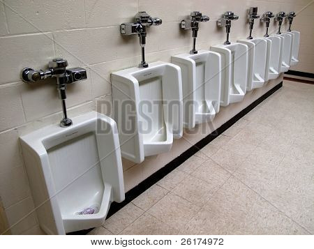 Row of white clean urinals in public restroom