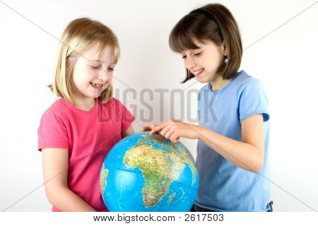 Two Sisters Looking At A Globe