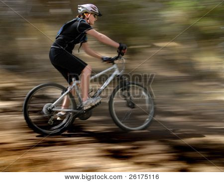 Young Woman Riding Mountain Bike in der Wildnis
