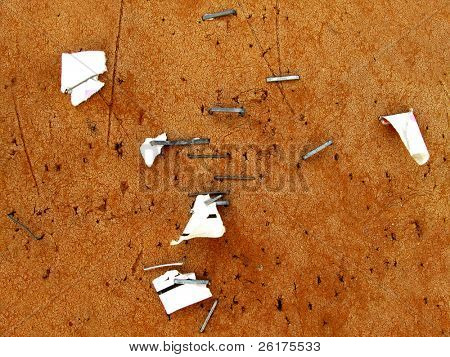 Cork or bulletin board with staples and paper attached