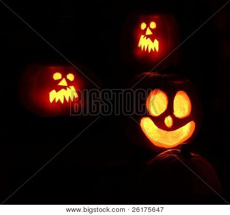 Dark Halloween night with carved pumpkin jack o lantern faces