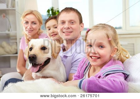 A happy family of four with a dog sitting on sofa, the focus is on the daughter