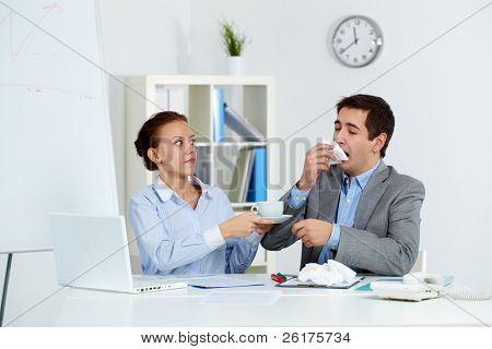 Imagem do empresário espirros enquanto seu parceiro ansioso, dando-lhe uma xícara de chá no escritório