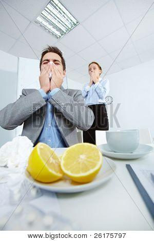 Imagem do empresário espirros enquanto seu parceiro no fundo olhando para ele com medo no escritório