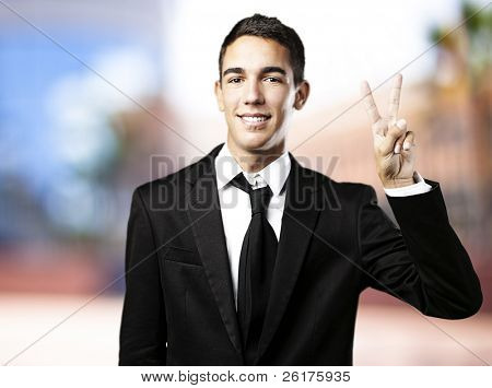 portrait of young business man doing victory symbol against a city background