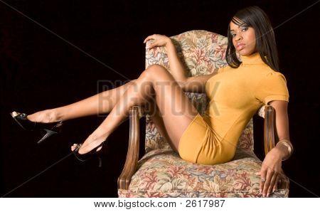 Chica glamour negra en silla