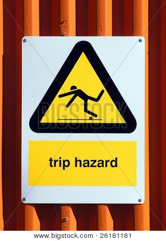Trip Hazard sign on an orange tin wall