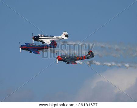 Three Yak-52 trailing smoke at the beginning of an aerobatic display