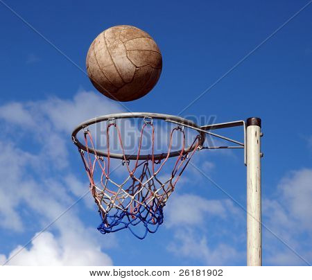 A netball frozen mid air above the goal