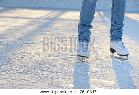 skater's legs standing on winter ice rink