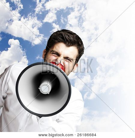 portrait of young man handsome shouting using megaphone against a blue sky background