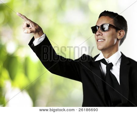 portrait of young business man pointing up against a nature background