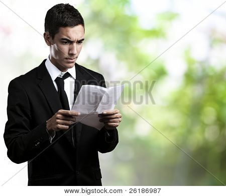 portrait of young business man reading a contract against a park background