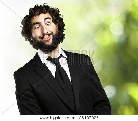 portrait of young business man showing the tongue against a nature background