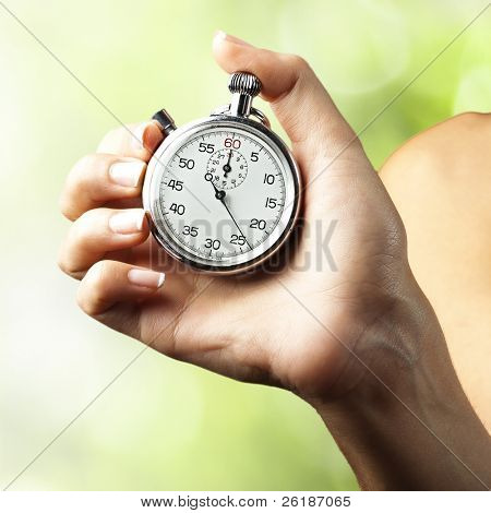 woman pushing stopwatch button against a nature background