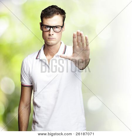 portrait of a handsome young man doing stop symbol against a nature background