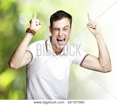 portrait of young crazy man shouting and pointing up against a nature background