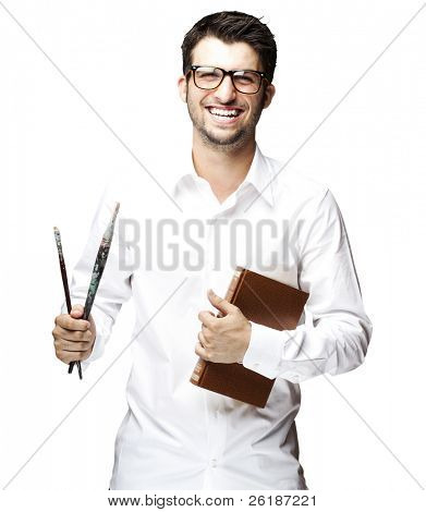 portrait of a handsome young student holding paintbrushes over white background