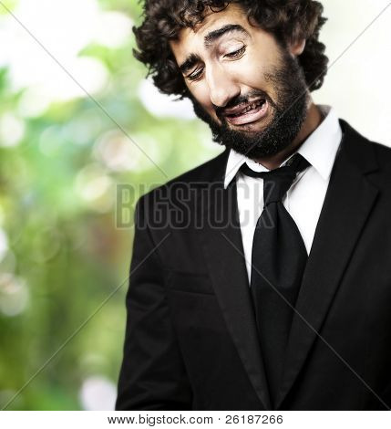portrait of business man crying against a nature background