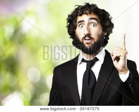 portrait of business man pointing up against a nature background