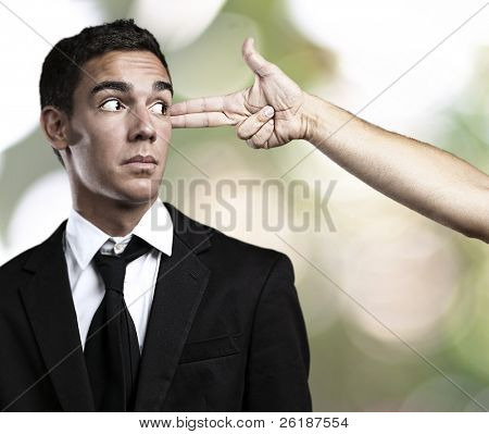 man gesturing gun pointing a business man against a nature background