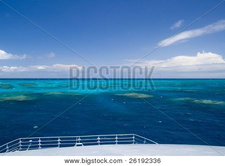 Shallow tropical reef against blue tropical sky with white clouds and flat water; Great Barrier Reef, Australia