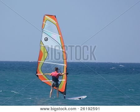 A water sportsman on a sailboard.