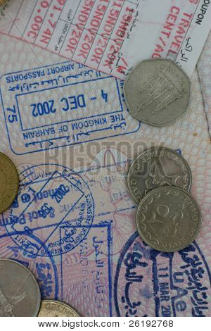 Gulf traveller: Coins of Qatar and the UAE with an air ticket and passport with entry/exit stamps for Bahrain and the UAE