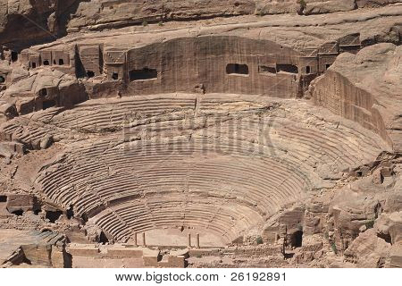 The amphitheatre cut into the rock at Petra, Jordan. The scale of the excavation can be seen from the Roman columns in the foreground at the front of the arena. Behind the seats there are some modest grave chambers.
