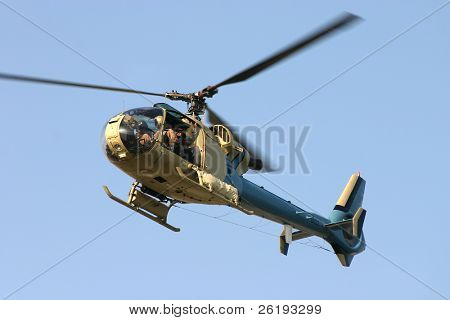 A civilian helicopter in flight with a crew member filming events below.