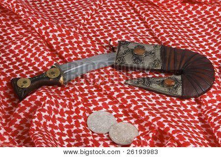 A traditional Arab dagger or khanjar, keffiyah headdress and Maria Theresia taler silver coins.