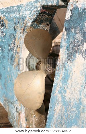 The propeller on a battered fibreglass boat in dry dock.